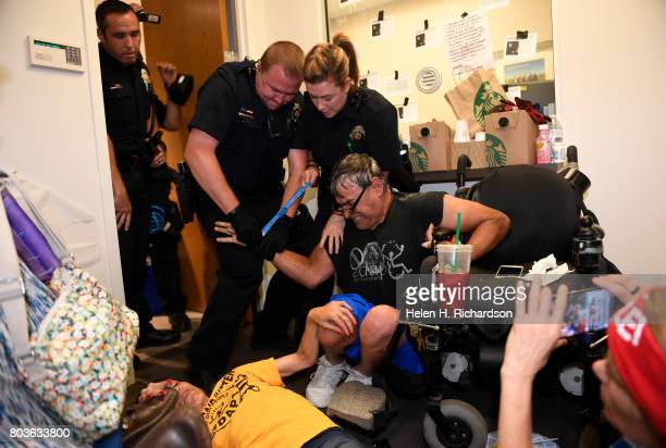 Lonnie Smith gets arrested by Denver police officers after refusing the vacate the offices of Senator Cory Gardner on June 29 2017 in Denver Colorado...