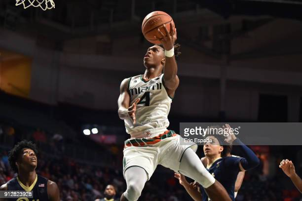 Lonnie Walker IV of the Miami Hurricanes drives to the basket while being defended by Parker Stewart and Marcus Carr of the Pittsburgh Panthers...