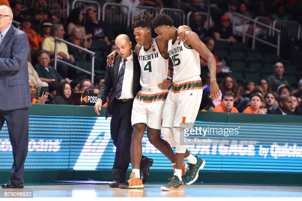 Lonnie Walker IV of the Miami Hurricanes is helped off the court by Ebuka Izundu and head athletic trainer Javier Jimenez during the first half...