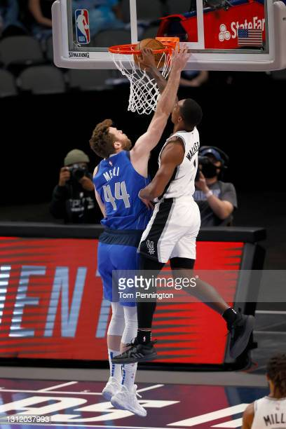 Lonnie Walker IV of the San Antonio Spurs drives to the basket and draws the foul against Nicolo Melli of the Dallas Mavericks in the second half at...