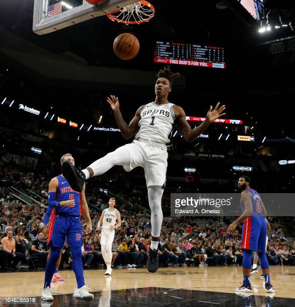 Lonnie Walker IV of the San Antonio Spurs reacts after a dunk around Luke Kennard of the Detroit Pistons during a preseason game on October 5 2018 at...