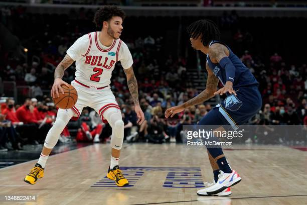Lonzo Ball of the Chicago Bulls dribbles the ball against Ja Morant of the Memphis Grizzlies in the first half during a preseason game at United...