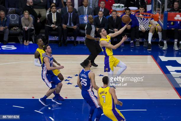 Lonzo Ball of the Los Angeles Lakers attempts a lay up against TJ McConnell and Ben Simmons of the Philadelphia 76ers in the first quarter at the...