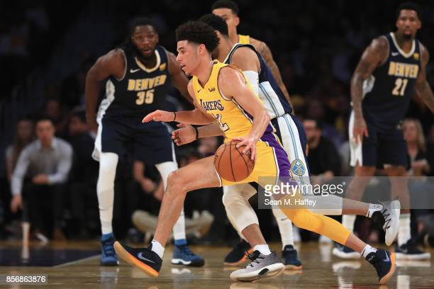Lonzo Ball of the Los Angeles Lakers dribbles the ball as Kenneth Faried and Wilson Chandler of the Denver Nuggets defend during the first half of a...