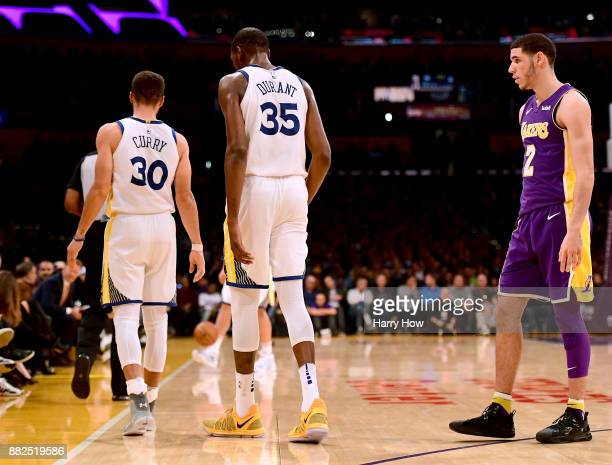 Lonzo Ball of the Los Angeles Lakers looks at Stephen Curry and Kevin Durant of the Golden State Warriors during the first half at Staples Center on...