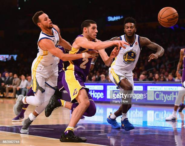 Lonzo Ball of the Los Angeles Lakers loses the ball as he drives to the basket between Stephen Curry and Jordan Bell of the Golden State Warriors...