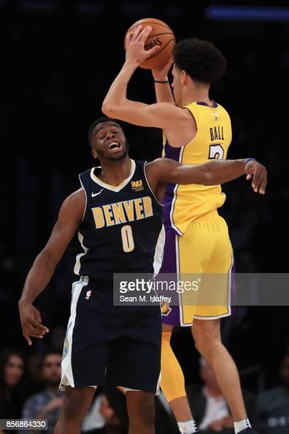 Lonzo Ball of the Los Angeles Lakers rebounds past Emmanuel Mudiay of the Denver Nuggets during the first half of a preseason game at Staples Center...