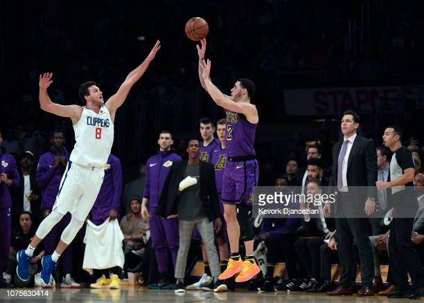 Lonzo Ball of the Los Angeles Lakers shoots and scores a three point basket in the closing second of the irate half against Danilo Gallinari of the...