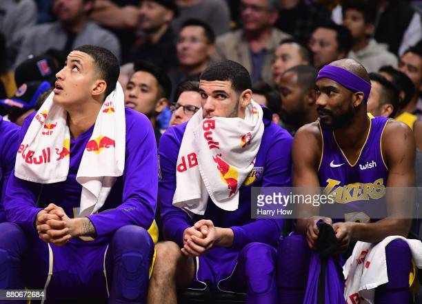 Lonzo Ball of the Los Angeles Lakers watches play from the bench with Kyle Kuzma and Corey Brewer during the second quarter in a 120115 LOS ANGELES...