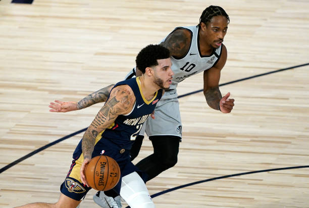 Lonzo Ball of the New Orleans Pelicans drives around DeMar DeRozan of the San Antonio Spurs during the second half at HP Field House at ESPN Wide...