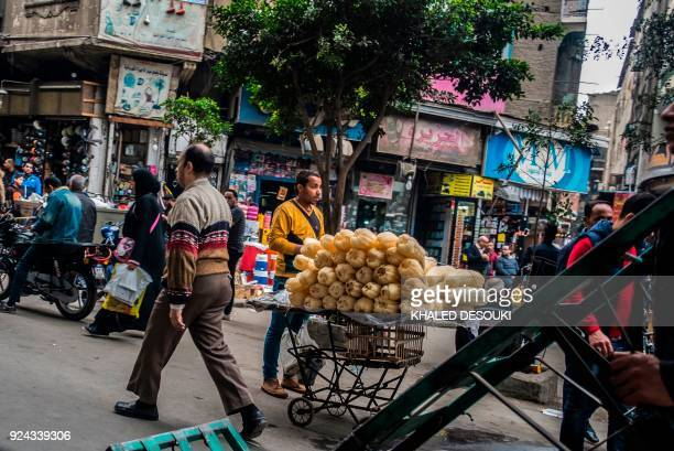 A loofah pedlar stands next to his cart in the AlAttaba market in the centre of the Egyptian capital Cairo on February 21 2018 While Sisi's...