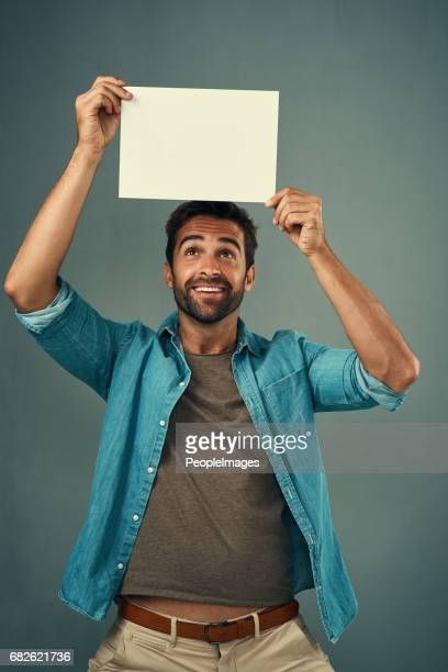 look at what we have over here - man holding paper imagens e fotografias de stock