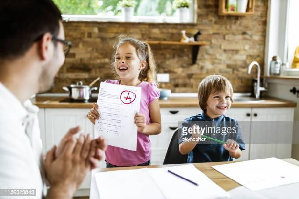 look daddy, i've got an a on my exam! - boletim escolar imagens e fotografias de stock