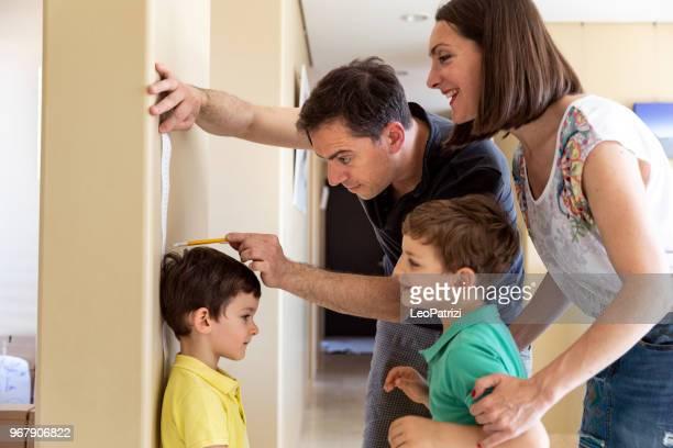 kijk hier hoe lang u bent! papa maatregelen zonen groei - lang lengte stockfoto's en -beelden