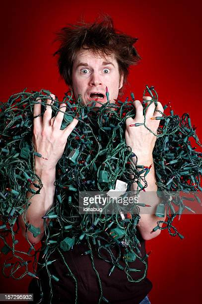 Look of Dread on Man with Tangled Christmas Lights