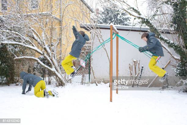 Look-alike teenagers jumping off swing in snowy garden