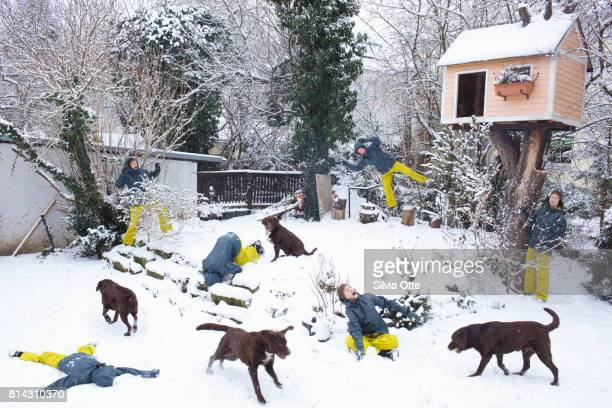 Look-alike teenagers playing with dog in snowy garden