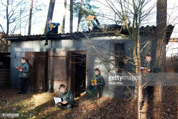 Look-alike teenagers sitting in front of shack in the woods reading