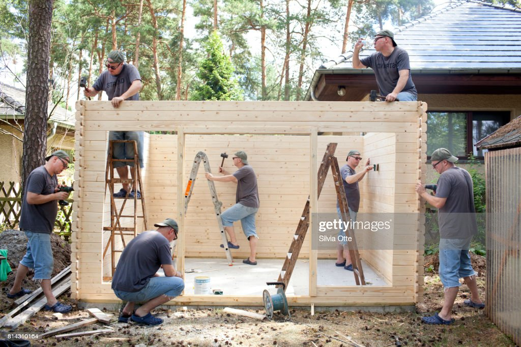 Look-alikes of middle-aged man painting, drilling and constructing a wooden house : Stock-Foto