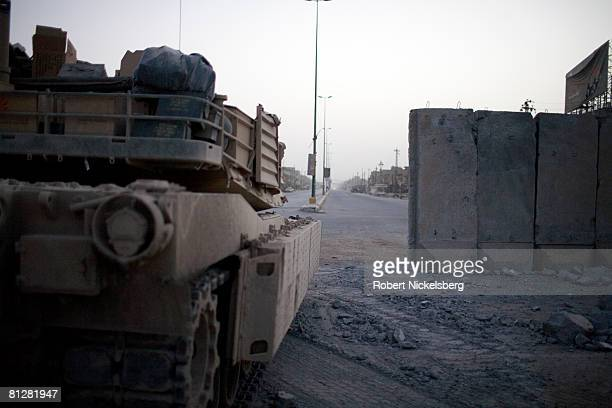 Looking across alQuds Street US Army M1 tanks guard the concrete barrier dividing Sadr City at dawn before Iraqi Armed forces move through to take...