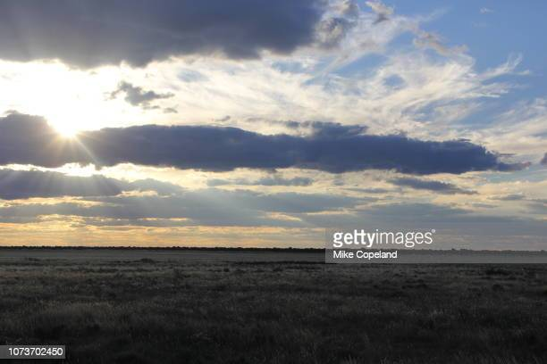 looking across the bosobogolo pan as the setting sun shines through clouds in the mabuasehube section of the kgalagadi transfrontier park in the kgalagadi district of botswana. - as stock pictures, royalty-free photos & images