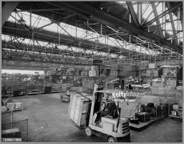 Looking across the interior of the haulage and parcels shed at British Road Services Depot, showing a fork lift truck driver moving crates in the...