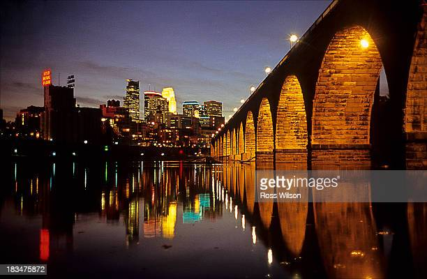 Looking across the Mississippi river and the Stone Arch Bridge to the downtown skyscrapers of Minneapolis at night. The iconic Stone Arch Bridge...