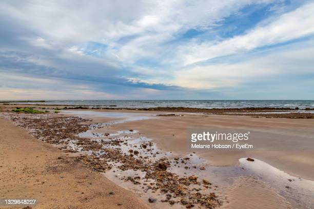 looking across the sandy beach and out to sea, at compton bay on the isle of wight - compton bay isle of wight stock pictures, royalty-free photos & images