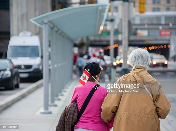 Looking after our elders Two women walk down the sidewalk on a busy city street during Canada's Day Celebrations Cityscape day