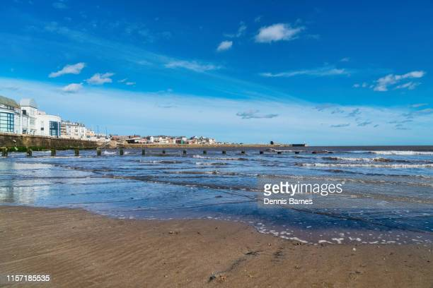 looking along bridlington beach towards harbour, yorkshire coast, england, uk - bridlington stock pictures, royalty-free photos & images