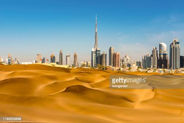 looking along desert towards the business district - dubai stock pictures, royalty-free photos & images