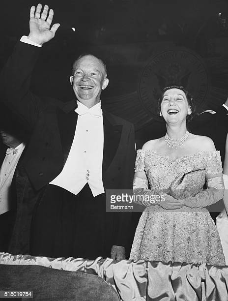 Looking as fresh and happy as when inaugural day dawned, President Eisenhower and the First Lady smile and wave to the throngs cheering them at the...