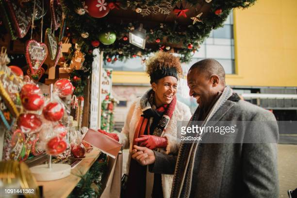 looking at a christmas market stall - christmas shopping stock photos and pictures