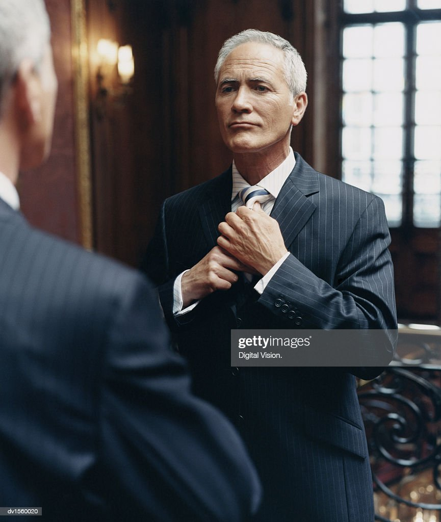CEO Looking at a Mirror in a Pinstripe Suit Adjusting His Tie : Stock Photo