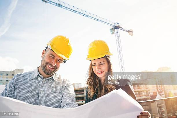 Looking at blueprints at the construction site
