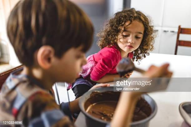 looking at brother making chocolate cake - easter sunday stock pictures, royalty-free photos & images