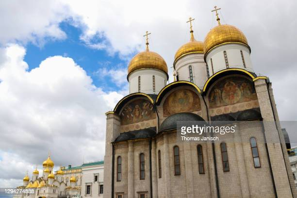 looking at cathedral of the dormition and cathedral of the annunciation inside the moscow kremlin with dark clouds approaching - state kremlin palace stock pictures, royalty-free photos & images