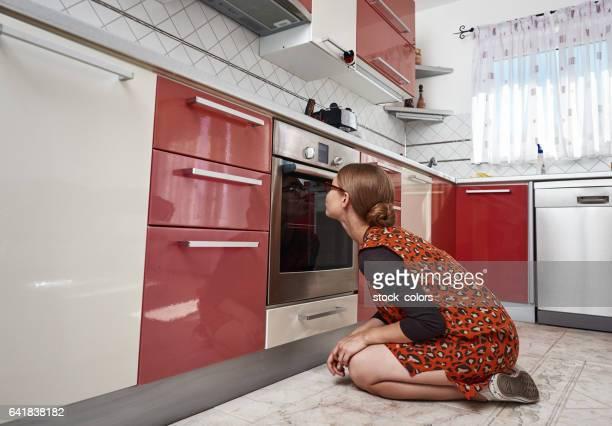 kijken naar haar voedsel tijdens het koken - ongeduldig stockfoto's en -beelden