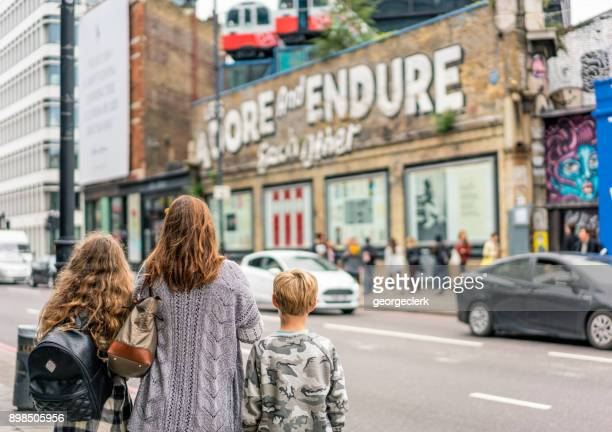 looking at street art in east london - shoreditch stock photos and pictures