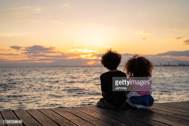 looking at sunset together - sister stock pictures, royalty-free photos & images