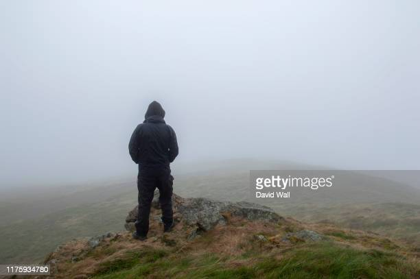 looking at the back of a hooded figure looking out on a foggy , moody day. on a bleak hillside in winter. with copy space. - mystery stock pictures, royalty-free photos & images