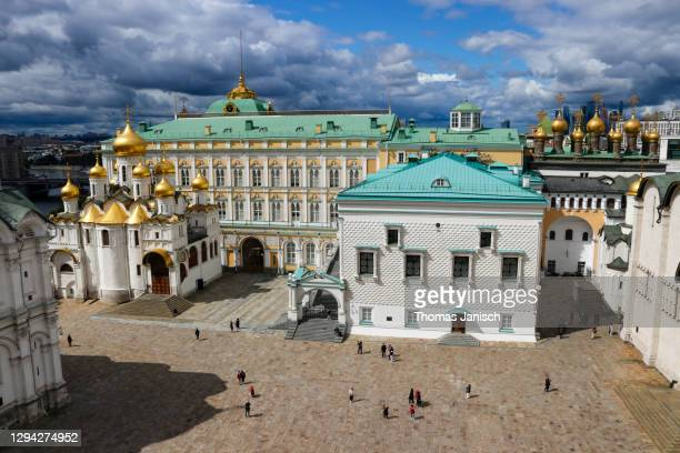 looking at the cathedral of the archangel and the cathedral of the annunciation inside the moscow kremlin with dark clouds approaching - state kremlin palace stock pictures, royalty-free photos & images