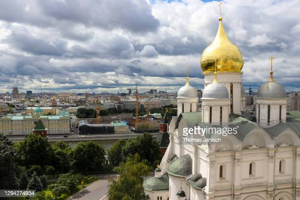 looking at the cathedral of the archangel inside the moscow kremlin with dark clouds approaching - state kremlin palace stock pictures, royalty-free photos & images