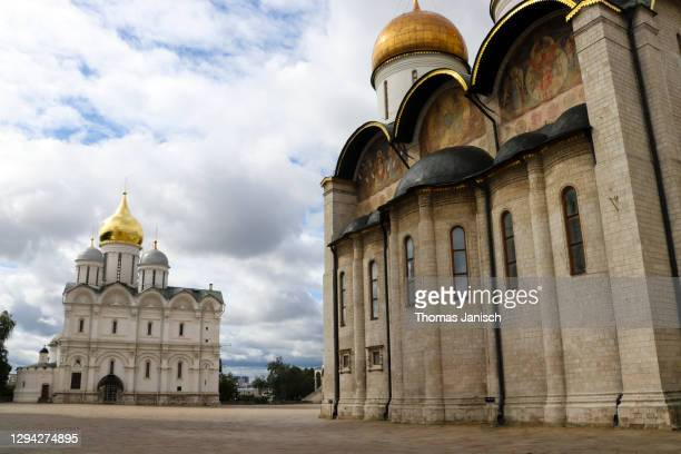 looking at the cathedral of the dormition and the cathedral of the archangel inside the moscow kremlin with dark clouds approaching - state kremlin palace stock pictures, royalty-free photos & images