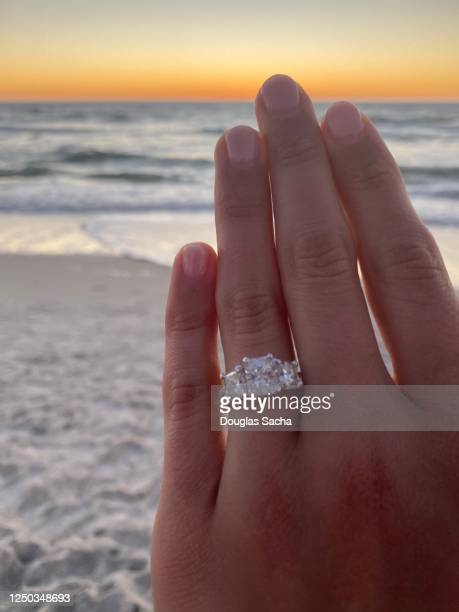 looking at the diamond ring while on the sunset beach - image title stock pictures, royalty-free photos & images