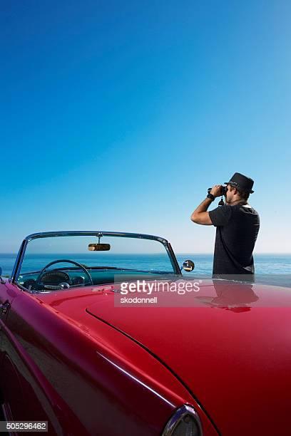 Schaut an das Meer von einem Cabrio Auto mit Fernglas