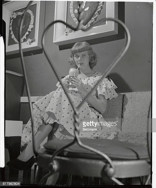 Looking demure as an oldfashioned valentine Dorothy Abbott drinking an icecream soda is seen through the frame of a wireback chair Her pink cotton...