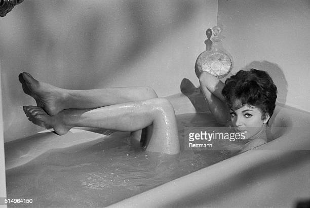 Looking Dewy-eyed, fresh and thoroughly appealing, British actress Joan Collins covers up coyly in her bath. The curvaceous lovely is appearing in...
