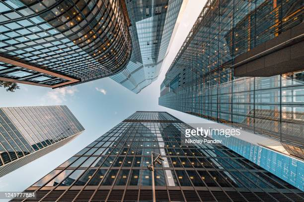 looking directly up at the skyline of the financial and business brand new district in central city of london on a bright sunny afternoon - creative stock image - building exterior stock pictures, royalty-free photos & images