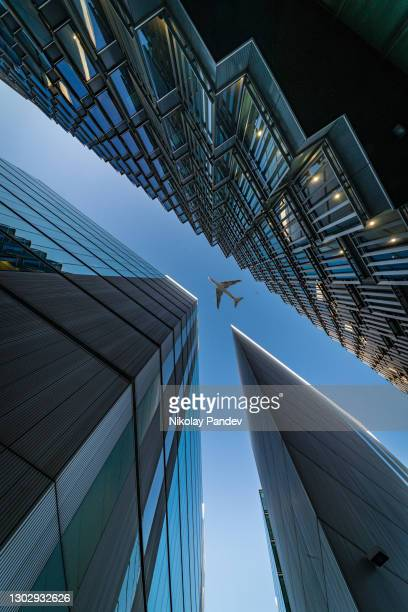 looking directly up at the skyline of the financial district in central london and passing airplane above - creative stock image - tower stock pictures, royalty-free photos & images